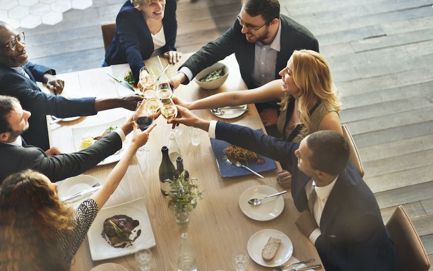 Corporate event planning: Team members cheers at a corporate dinner
