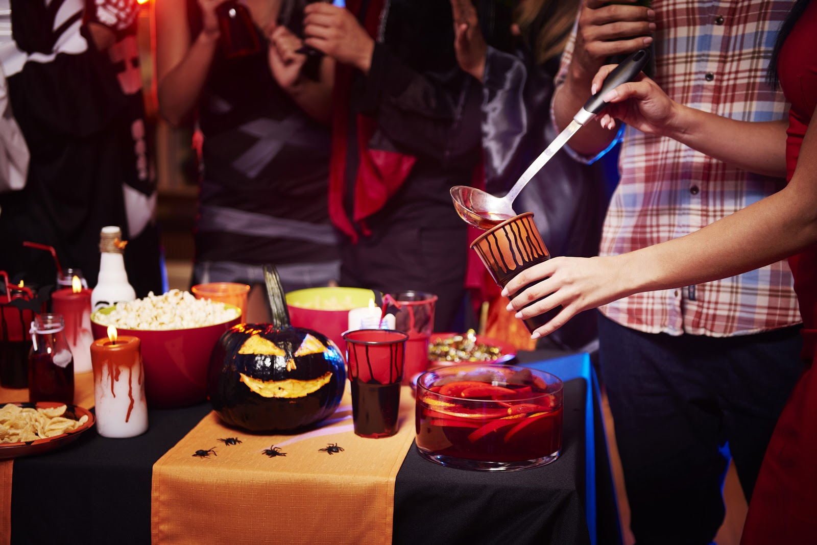 Party goers pour punch while discussing Halloween party ideas.