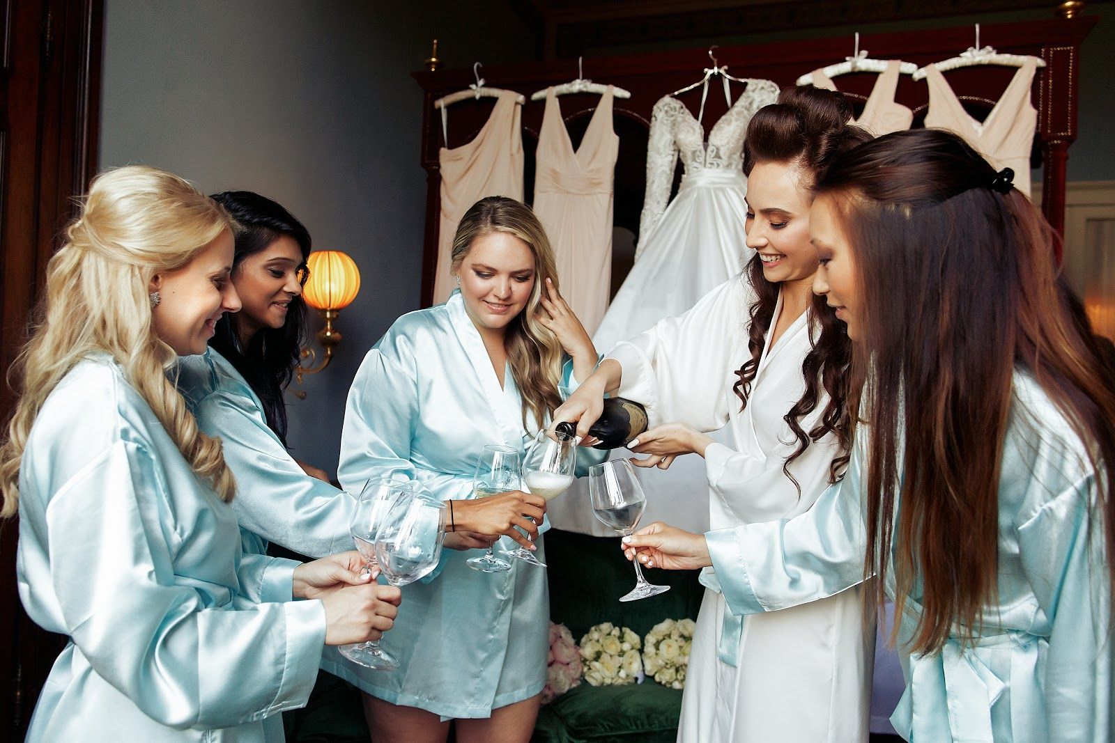 bridesmaid proposal ideas: Bride and bridesmaids in silk robes while having champagne