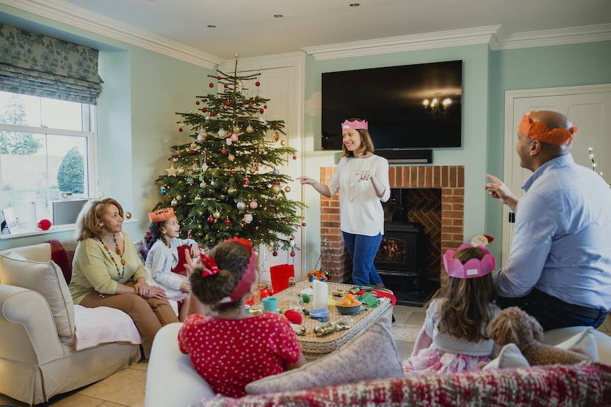 Guests at a Christmas party play charades and other holiday party games