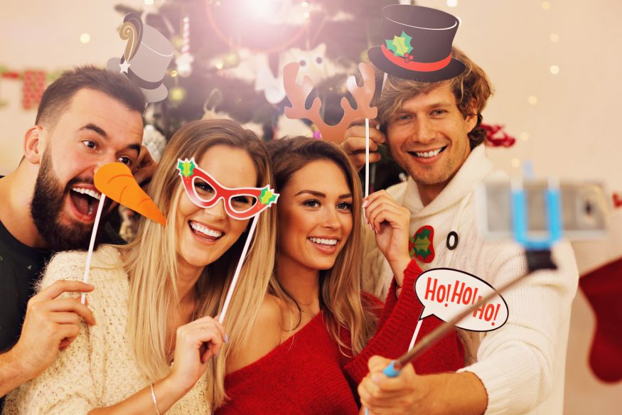 Holiday party ideas: Guests hold photo props in front of the Christmas tree