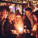 Christmas party ideas: A group celebrates with sparklers and Christmas lights behind them