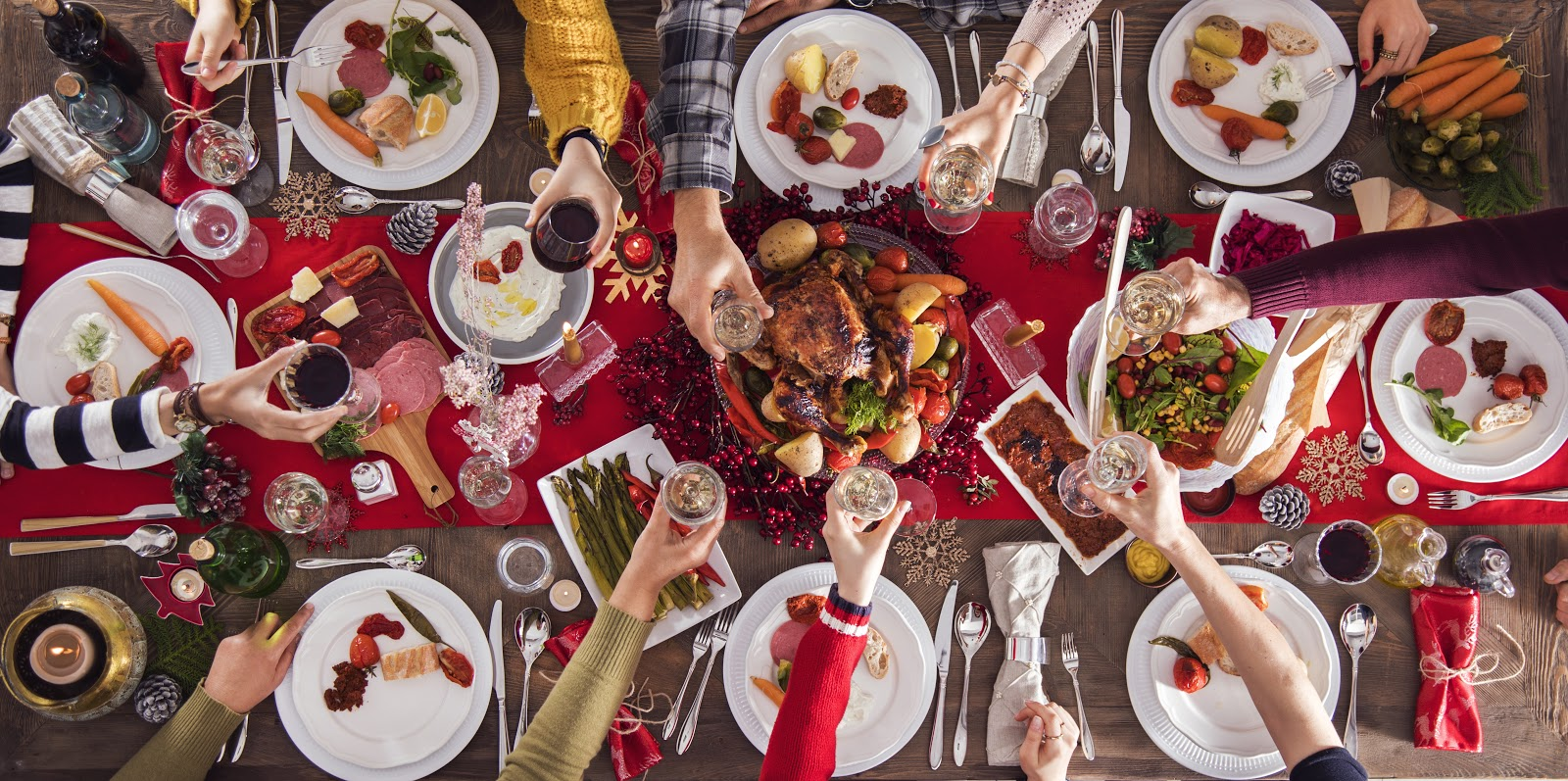 Christmas party ideas: Hands cheers over a Christmas dinner table