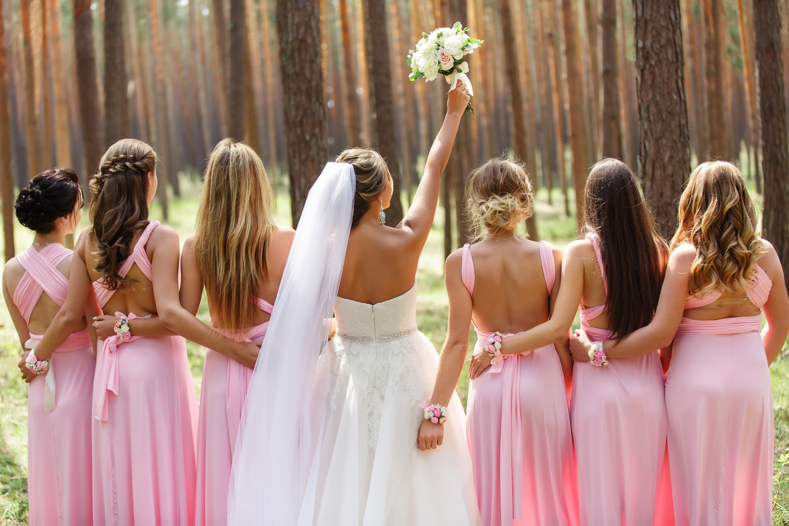 Bride with her bridesmaids in pink dresses during the wedding day