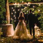 A bride and groom stand at a rustic alter in the woods