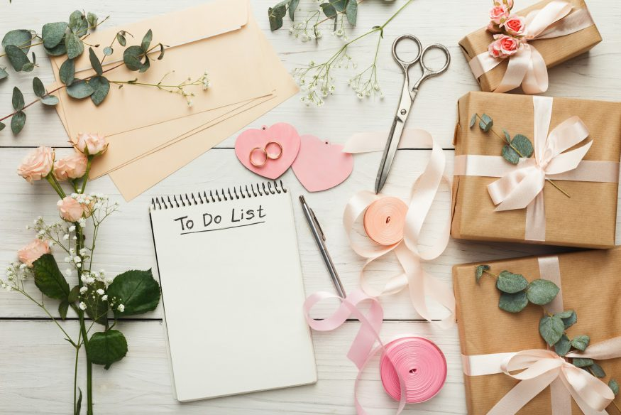 Party planning: a to-do list surrounded by fits, ribbon, envelopes, and flowers