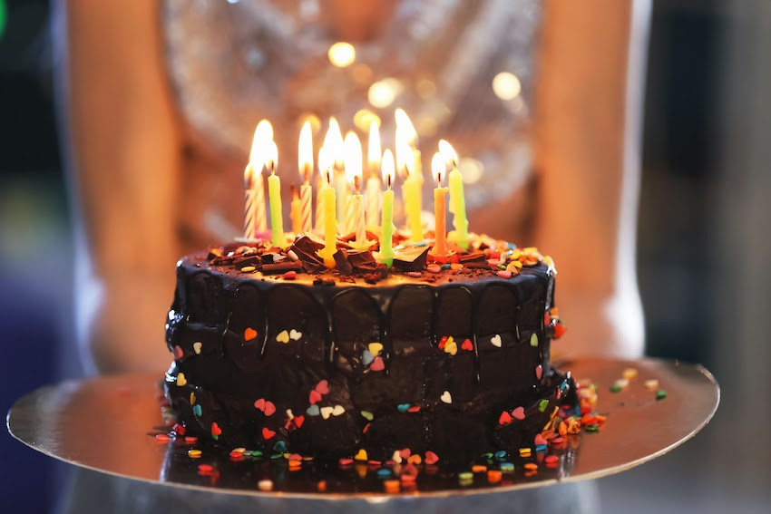 A woman carrying out a birthday cake with candles