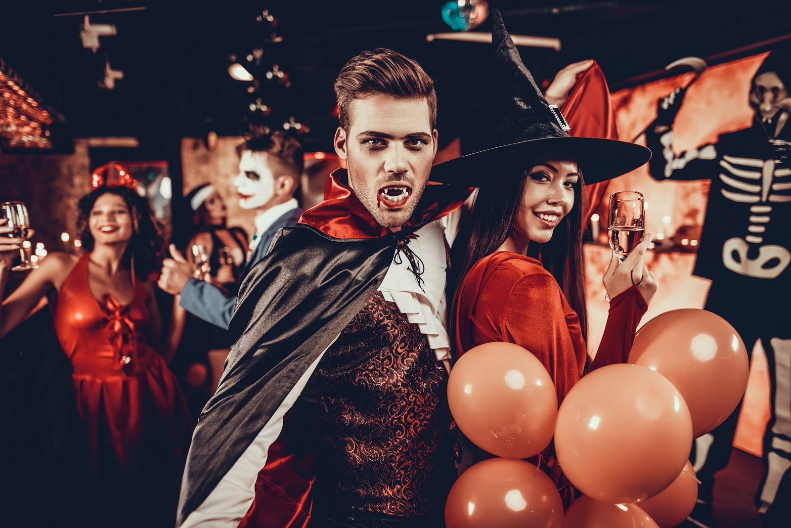 Adults dressed up as vampires, witches, and devils for a halloween party