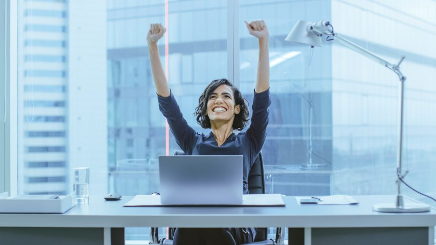 A business woman celebrates at her desk