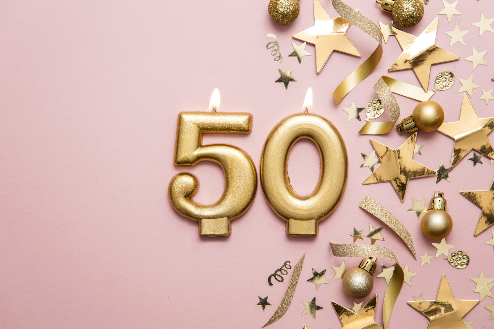 50th birthday party ideas: Number 50 gold candles with gold confetti and baubles on the side against a pink background