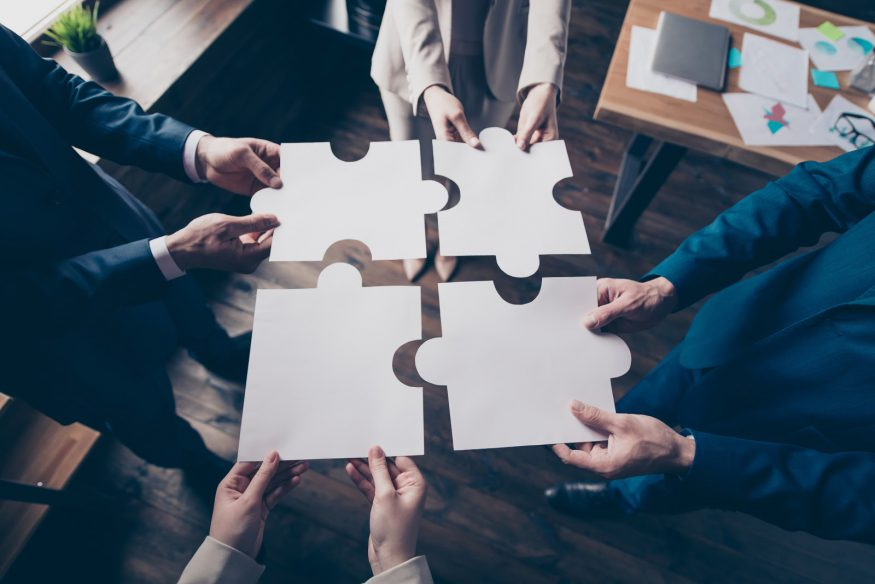 Corporate event ideas: Business people put together the pieces to an oversized puzzle