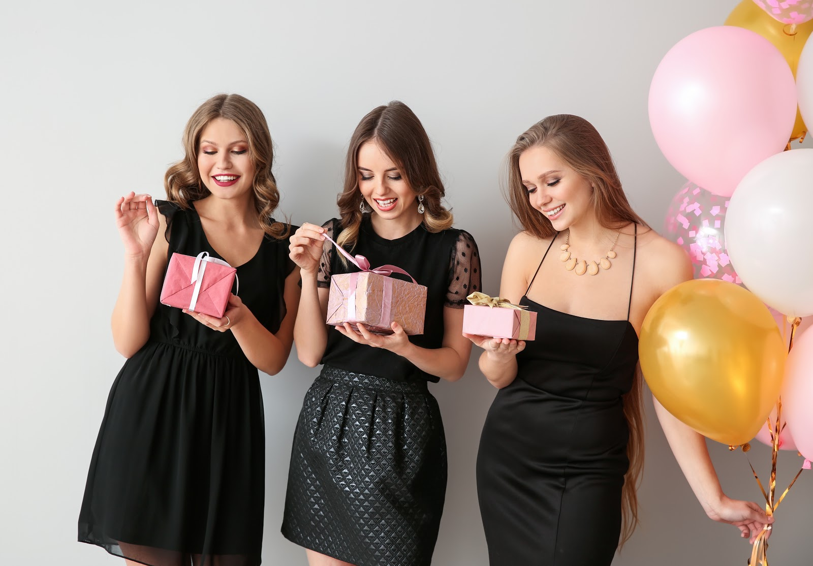 bridesmaid proposal ideas: Three women holding gifts and balloons