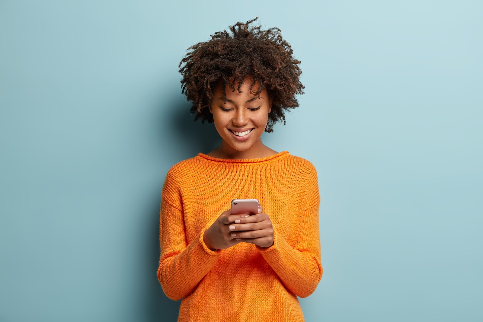 text message invitations: Smiling woman typing a text message