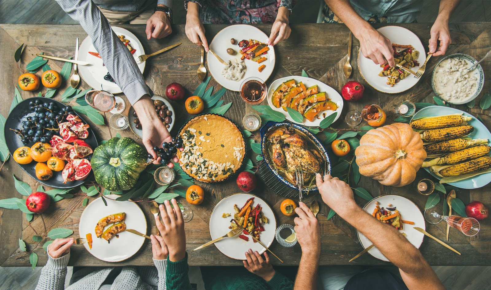 Hands reach across a Thanksgiving table for food