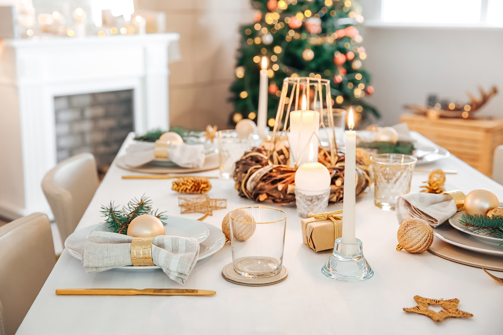 Christmas decorating ideas: A table with white and gold place settings and a Christmas tree in the background