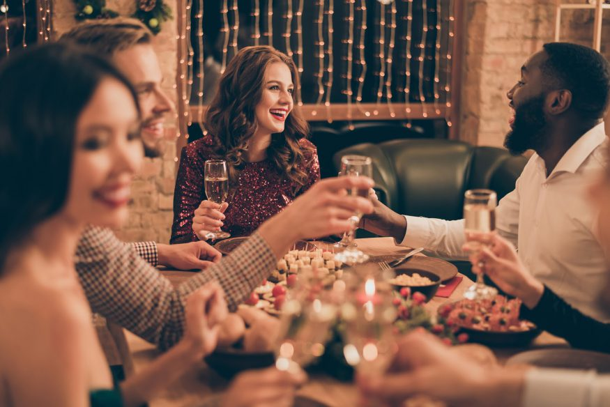 Guests hold up their champagne glasses at a holiday dinner party