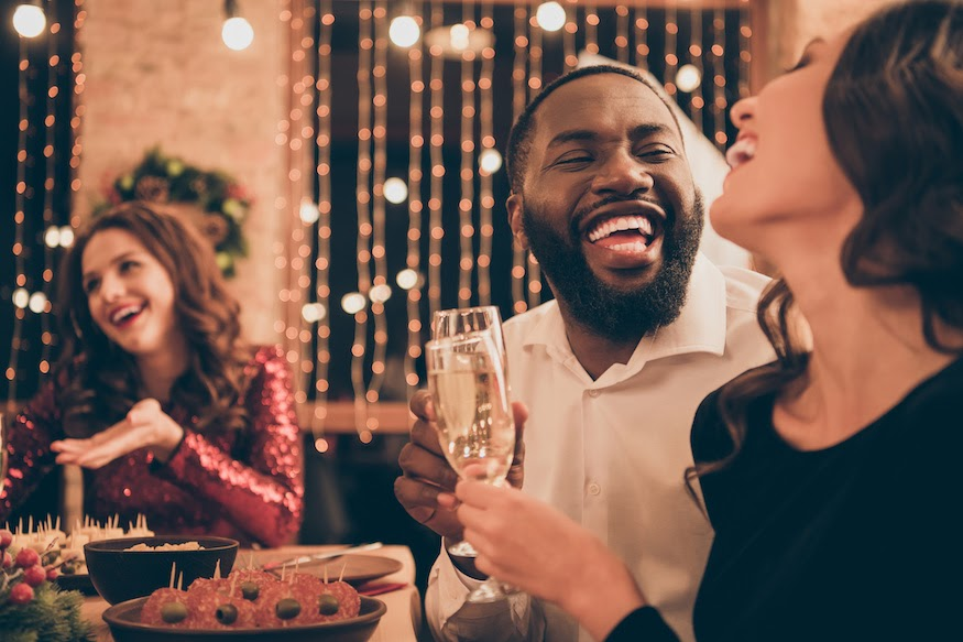 Guests hold champagne glasses and talk at a holiday dinner party