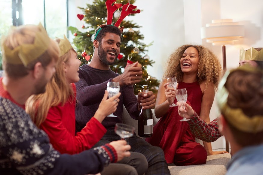 Guests sit around a living room playing holiday party games