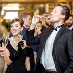 Guests in evening gowns and tuxedos raise champagne glasses at a formal event
