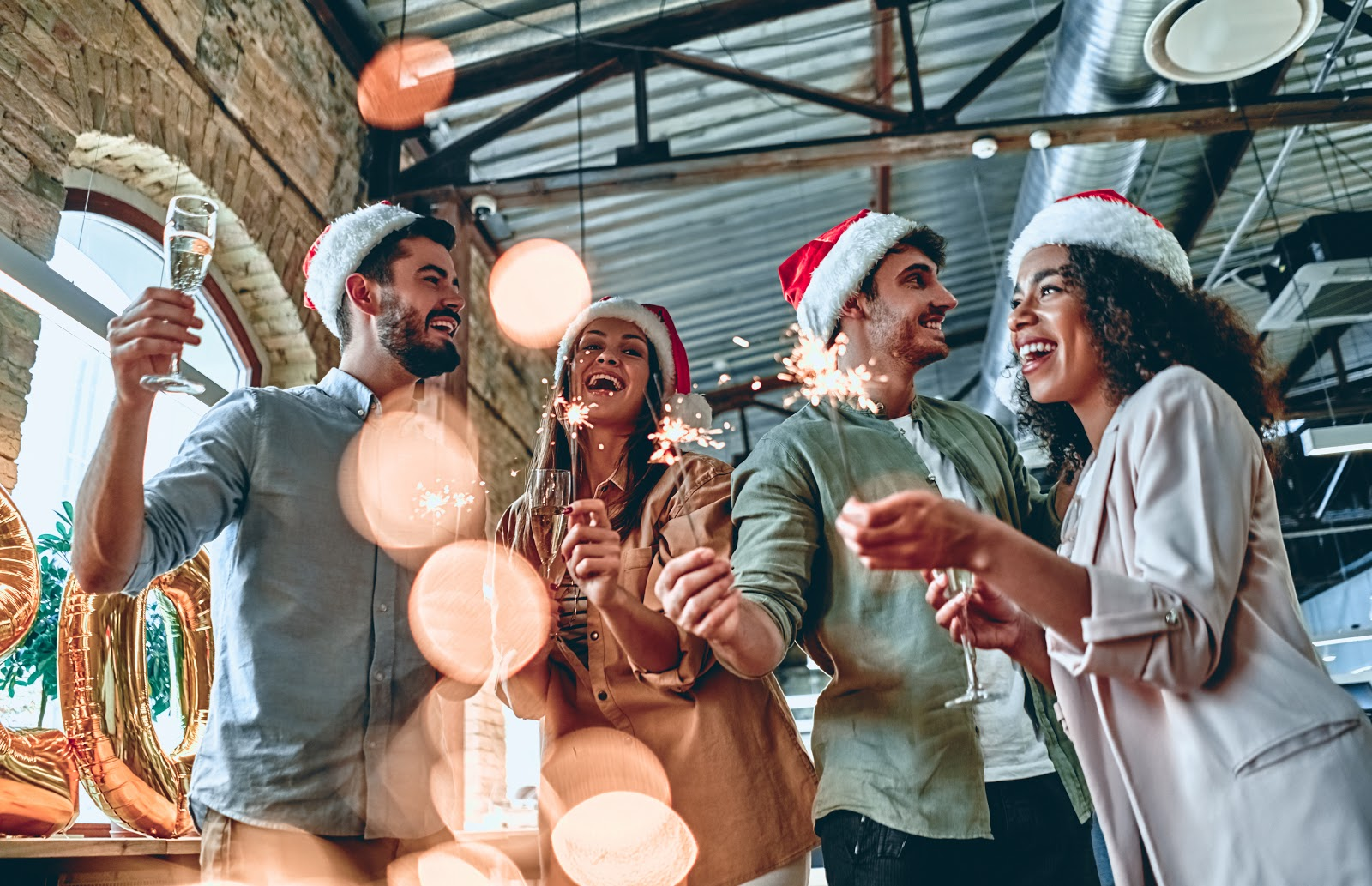 Christmas party ideas: Guests hold sparklers and champagne flutes at a holiday celebration