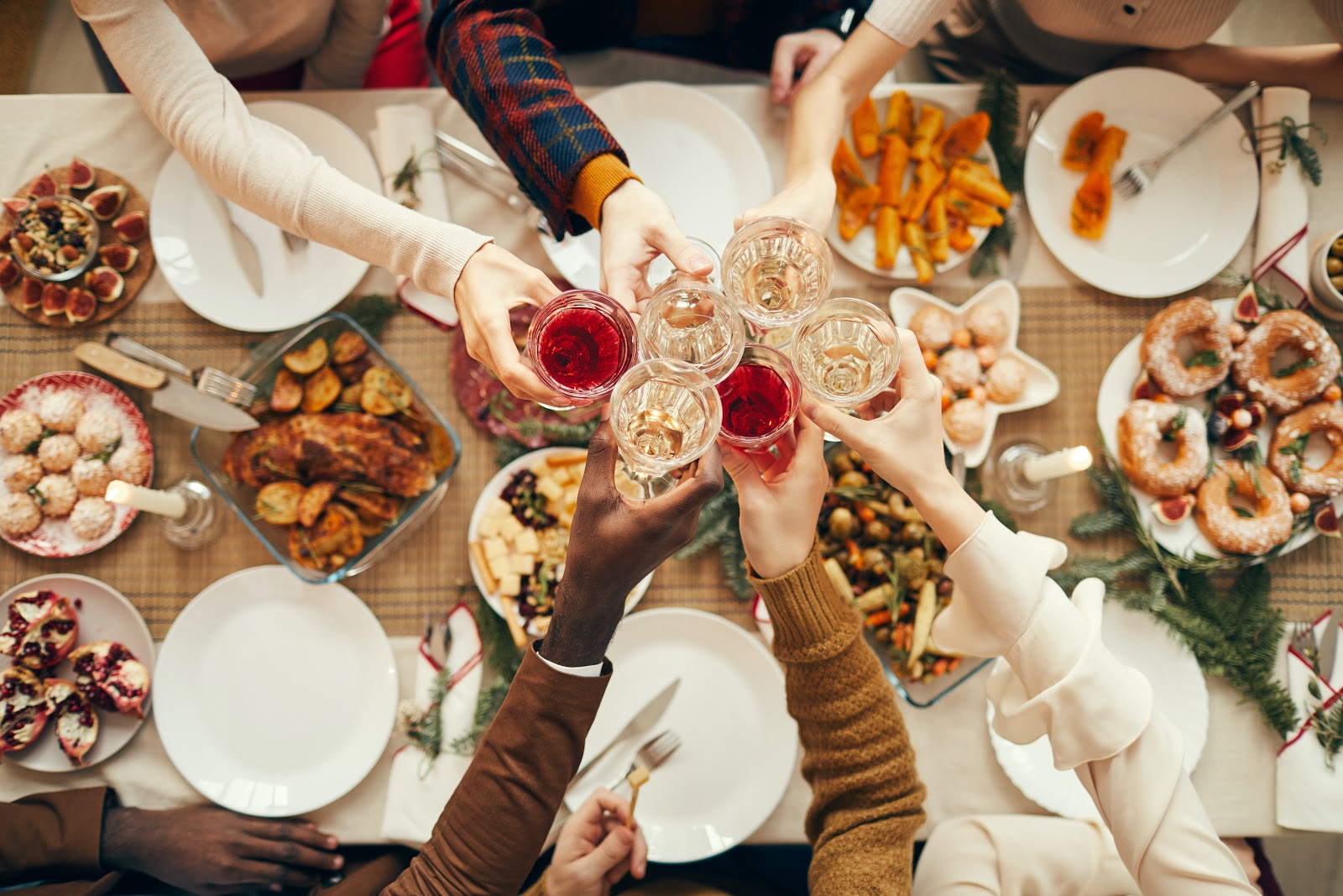 Christmas party food ideas: Guests raise their glasses over a Christmas party dinner table