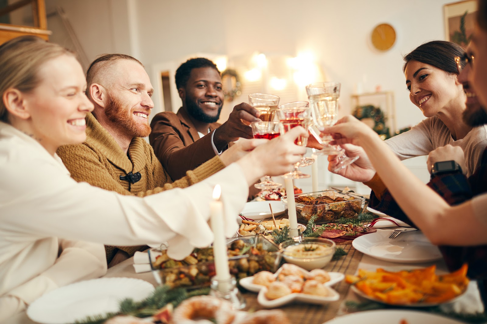 Non-traditional thanksgiving dinner ideas: An eclectic group of friends raise their glasses over the Thanksgiving table