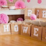 """Baby shower ideas: A table of cupcakes behind a display of gift bags that spell out """"BABY SHOWER"""""""