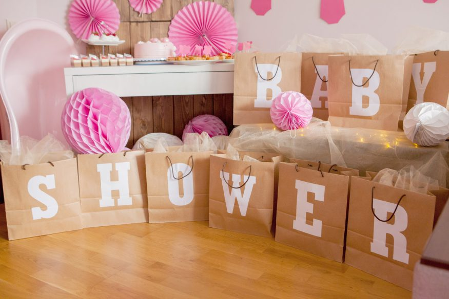 """Baby shower ideas: A table of cupcakes behind gift bags that spell out """"BABY SHOWER"""""""