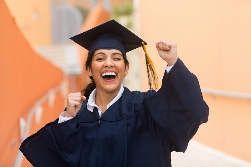 A smiling graduate pumps her fists in excitement