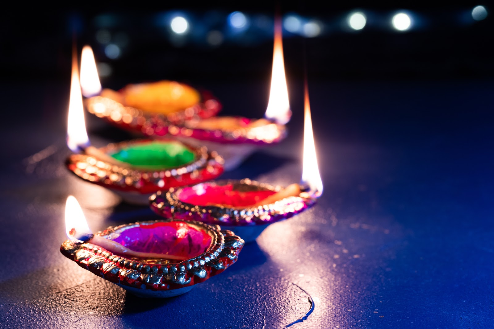 Diwali party ideas for decorations: a row of colorful diya lit up