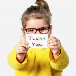 Thank you card ideas: A little girl holds up a handmade thank you card