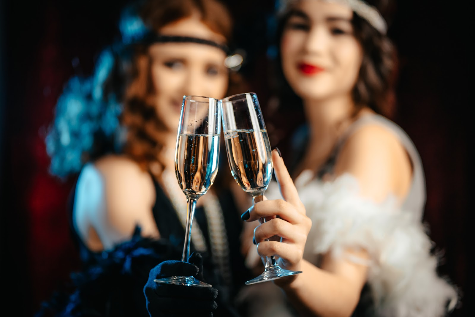 Two women holding champagne glasses in a Great Gatsby party
