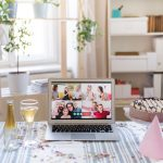 How to host a virtual event: A table set for a party with a laptop showing a virtual video meeting