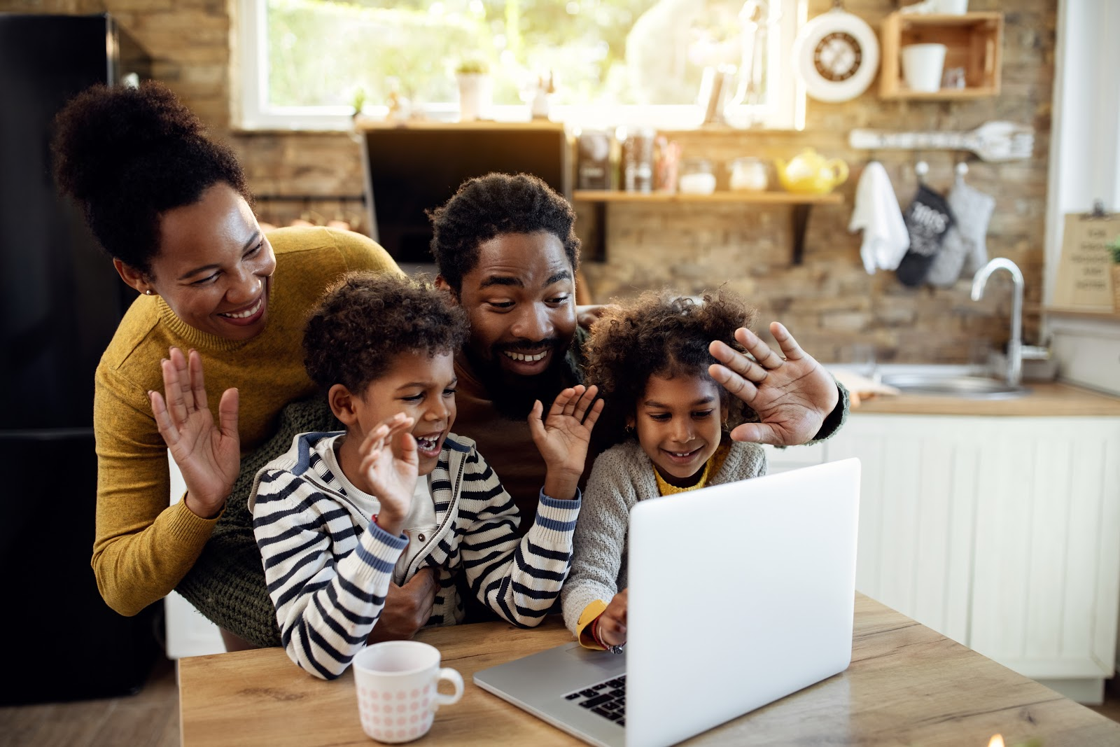 Virtual family games: Happy family and waving during a video call