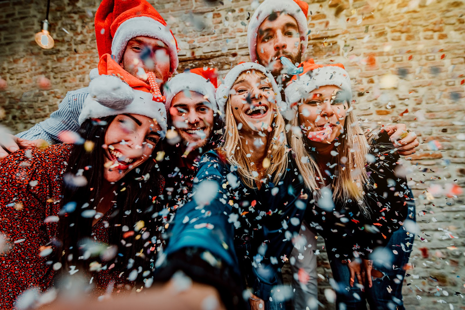 text message invitations: Group of friends wearing Santa hats taking a photo while surrounded by confetti
