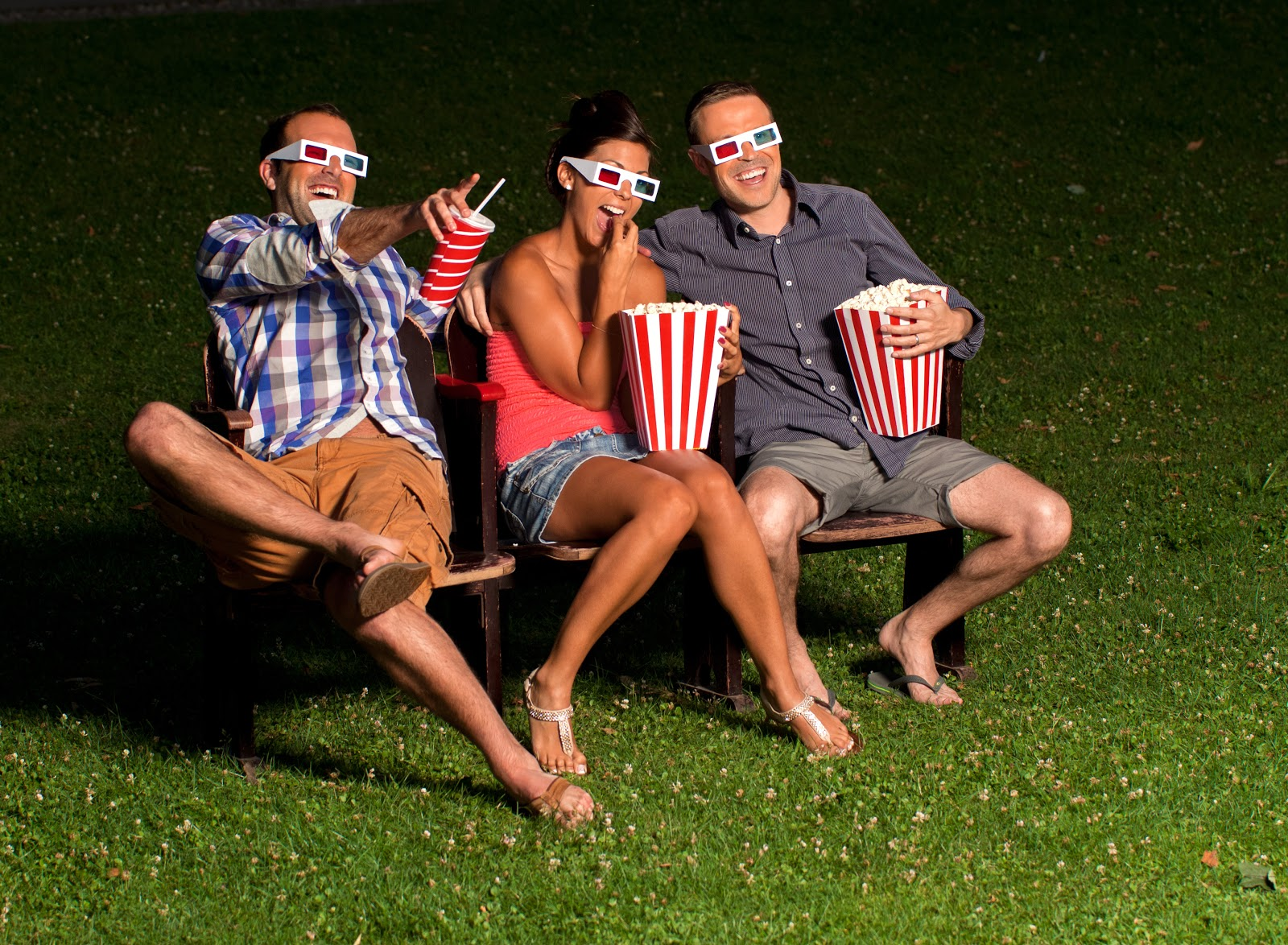 outdoor movie night: Friends watching a 3D movie outdoors while eating popcorn