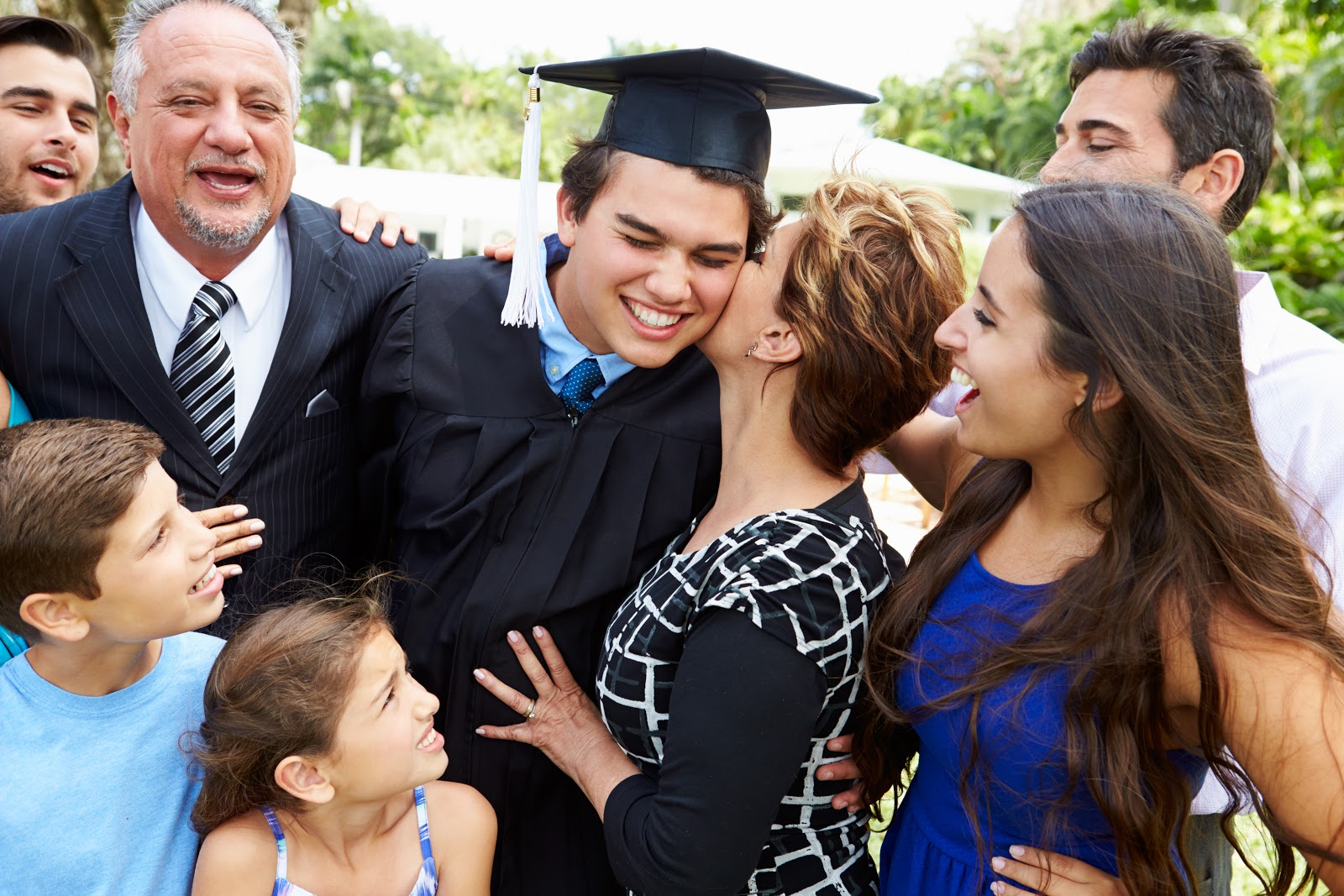 Mom kissing his son on graduation day