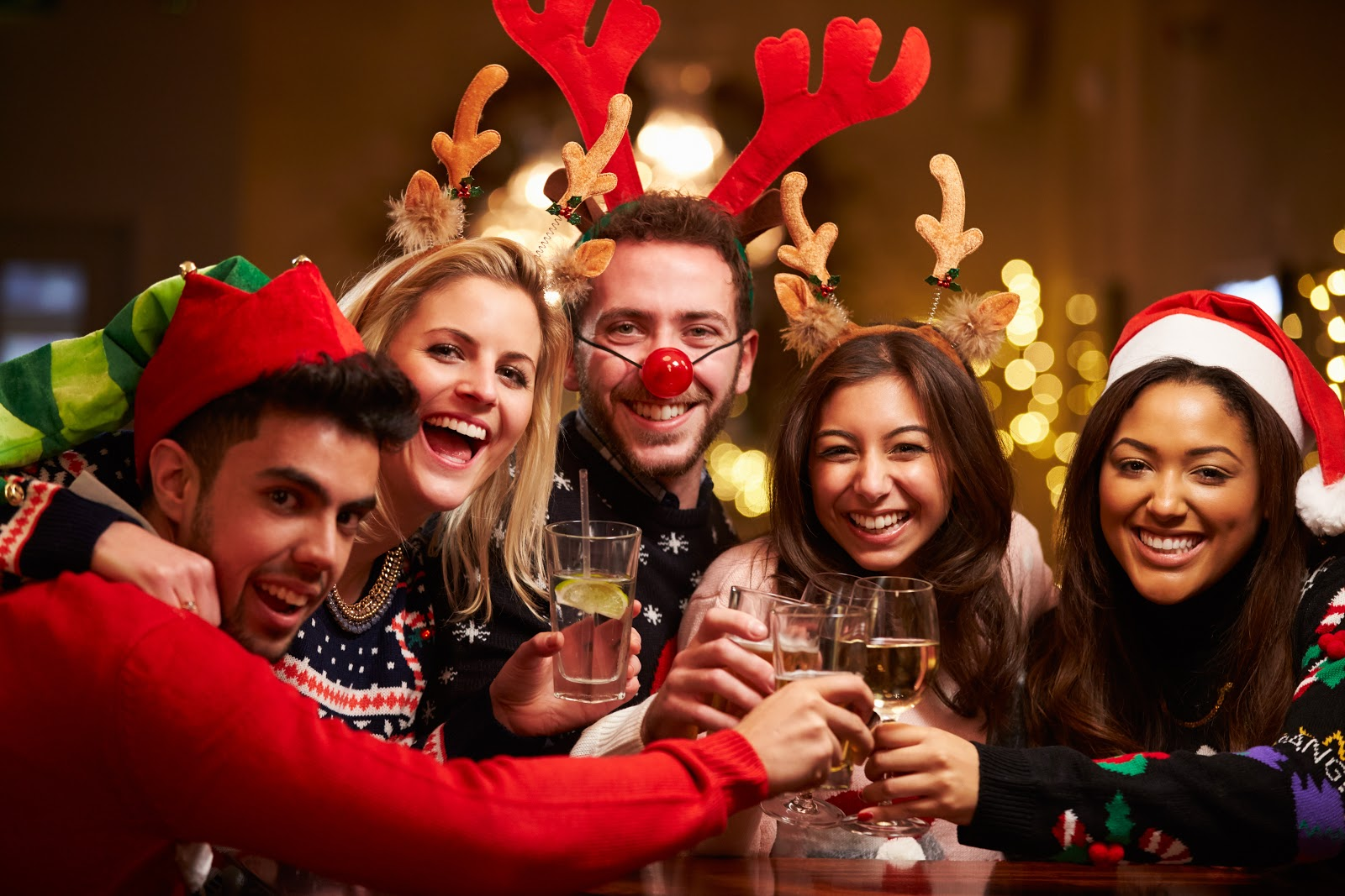 Christmas party ideas: A group wears reindeer antlers and holds up their glasses