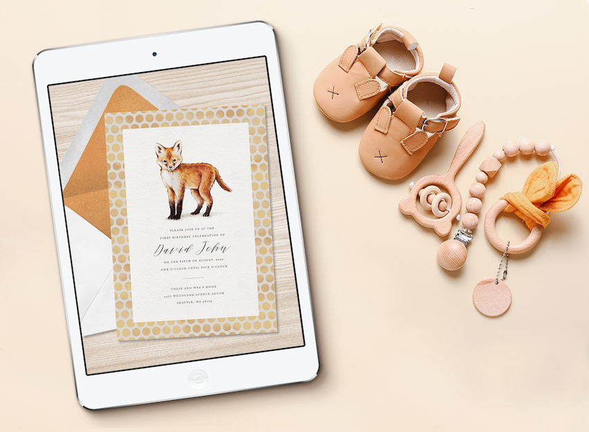 An online baby shower invitation displayed on a tablet screen, next to baby shoes and toys