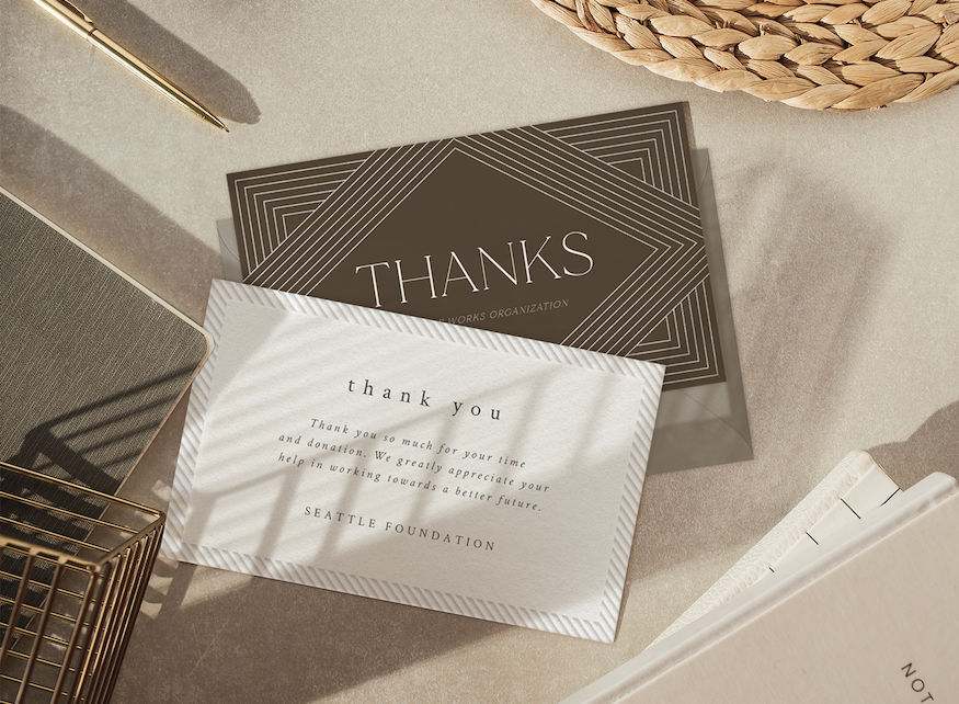 Two business thank you cards on a desk, surrounded by office supplies