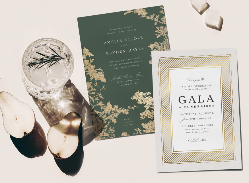 Two formal event invitations with a champagne coup and a pear