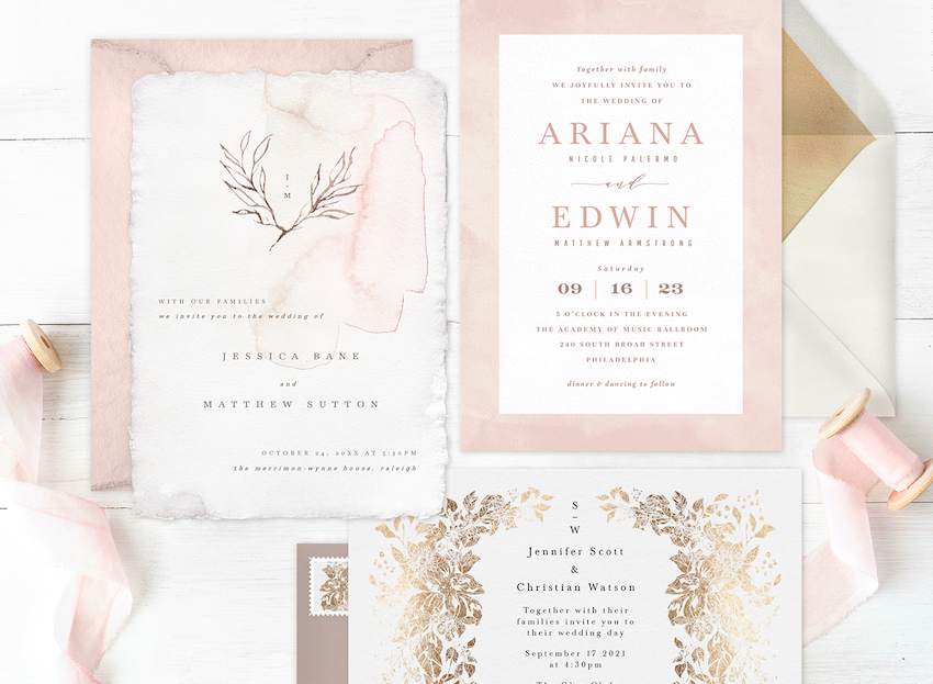 three affordable wedding invitations laid out on a wood table with ribbon and envelopes