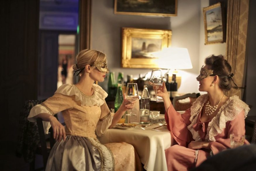 Two women at a masquerade murder mystery dinner party
