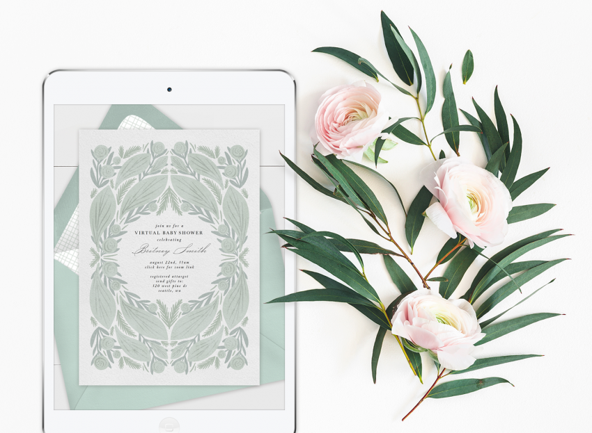 Virtual baby shower invitation on an iPad with florals laying next to it