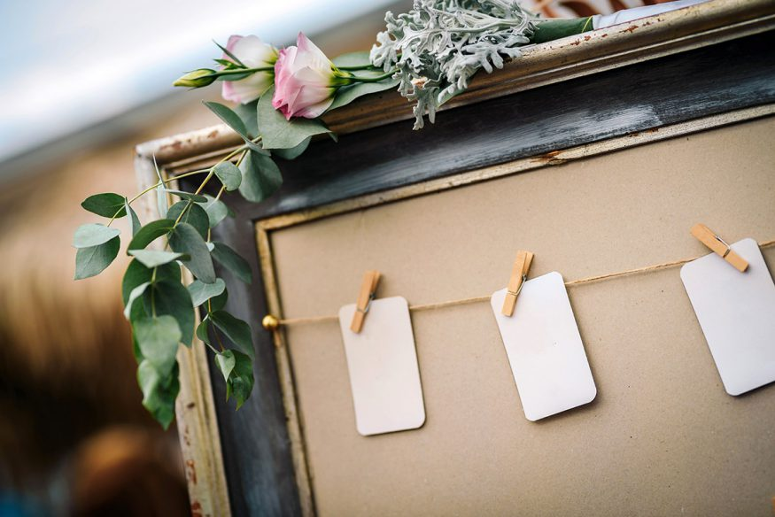 wedding guest list: cards pinned on a board using wooden clothespins