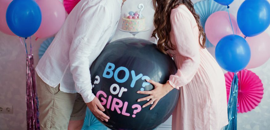Gender reveal party: couple holding a gender reveal balloon
