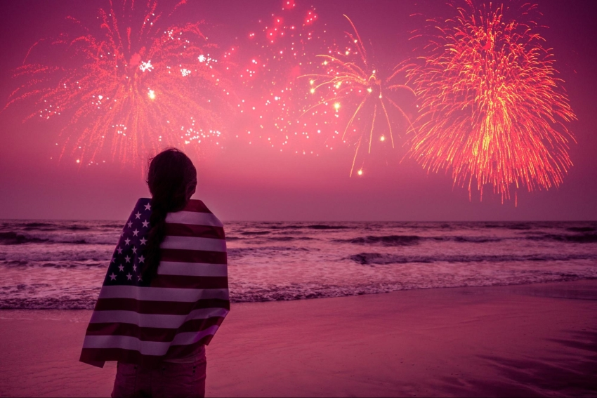 4th of July party invitations: Woman watching fireworks at the beach with an American flag wrapped around her shoulders