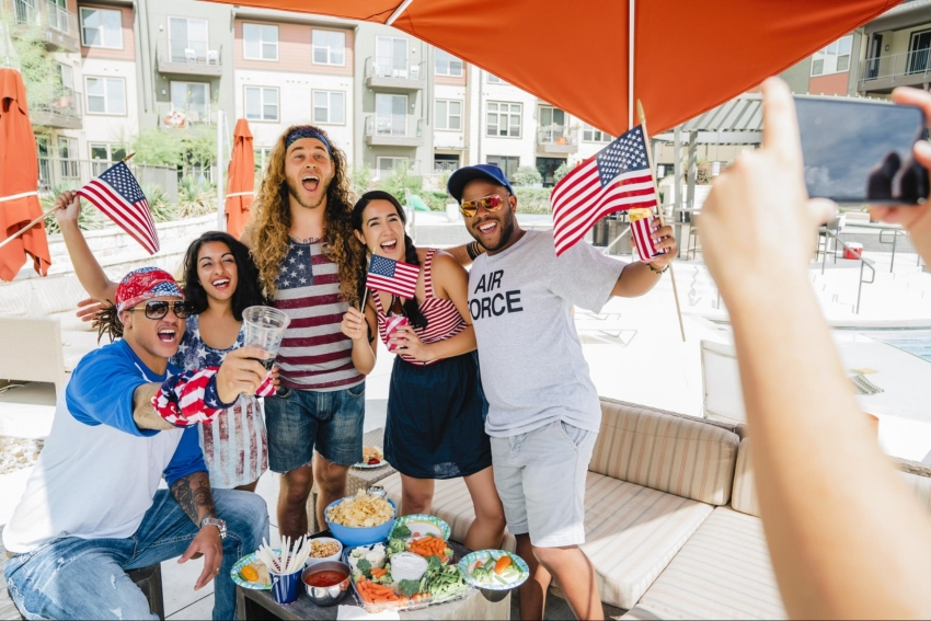 4th of July party invitations: Friends wearing patriotic cloths and waving flags while getting their picture taken