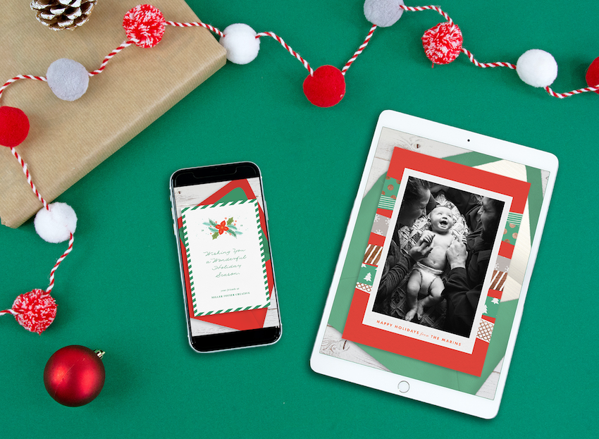 Digital holiday cards displayed on a tablet and phone, surrounded by garland