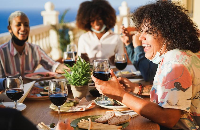 People eating and drinking red wine while wearing protective masks